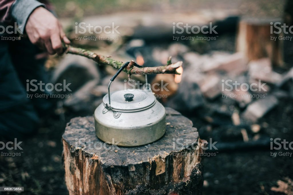 Male hand picking up hot kettle from campfire with branch. royalty-free stock photo