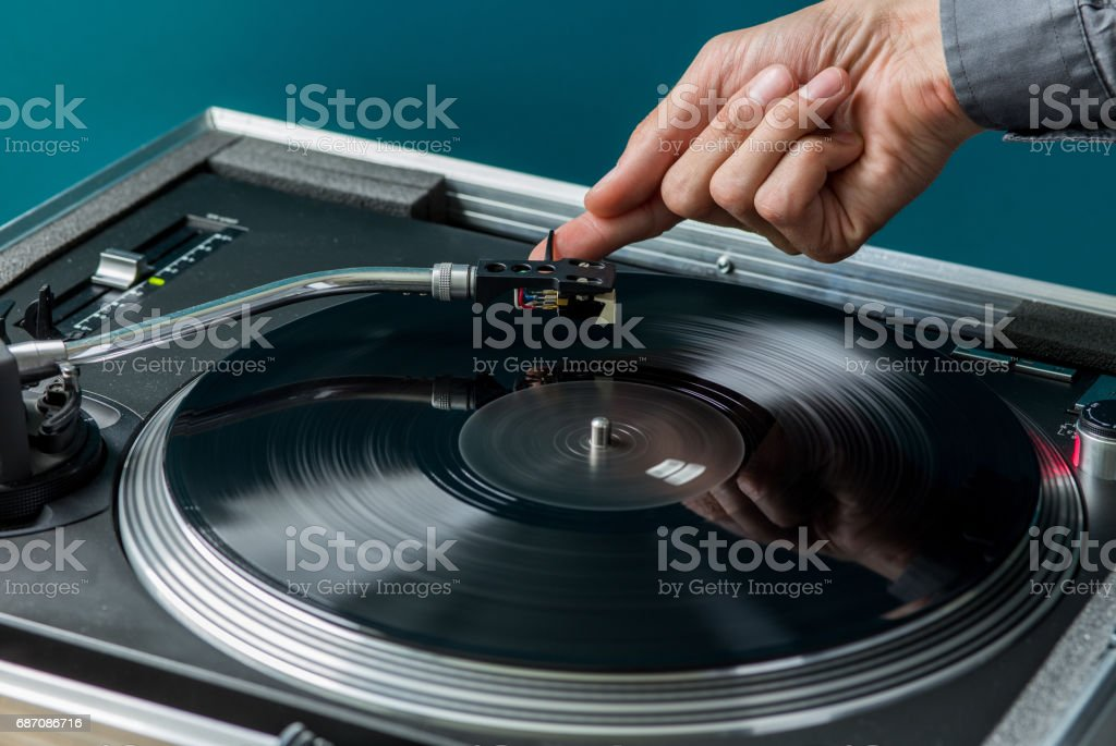 Male Hand Placing Stylus on Vinyl Record stock photo