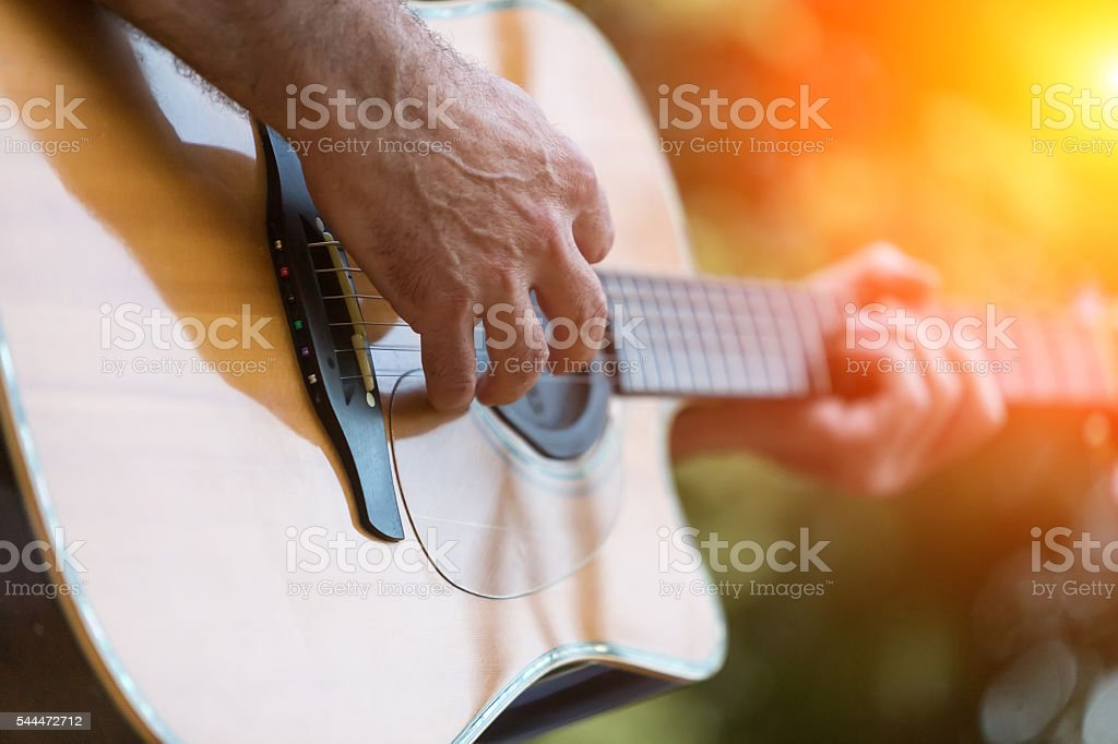 Male hand playing on acoustic guitar stock photo