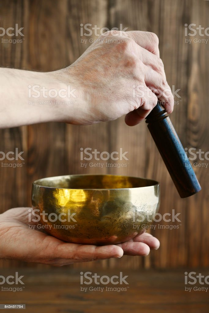 Male hand playing on Tibetan handcrafted singing bowls stock photo