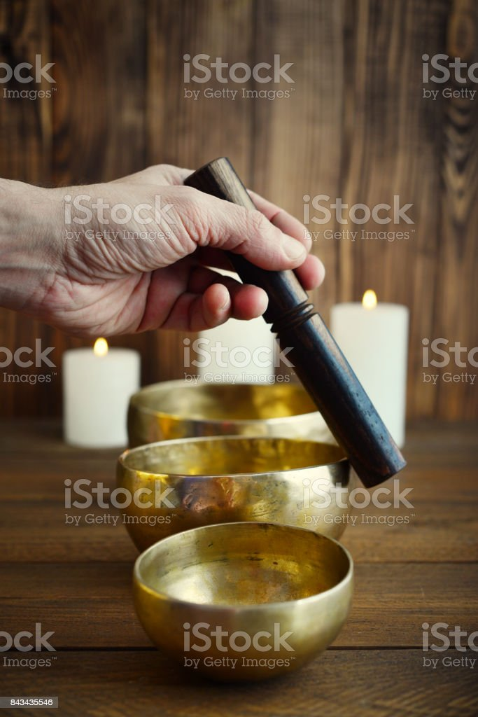 Male hand playing on Tibetan singing bowls stock photo