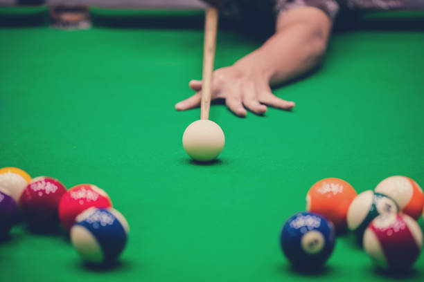 male hand playing snooker or pool game on green table. - pool cue stock photos and pictures