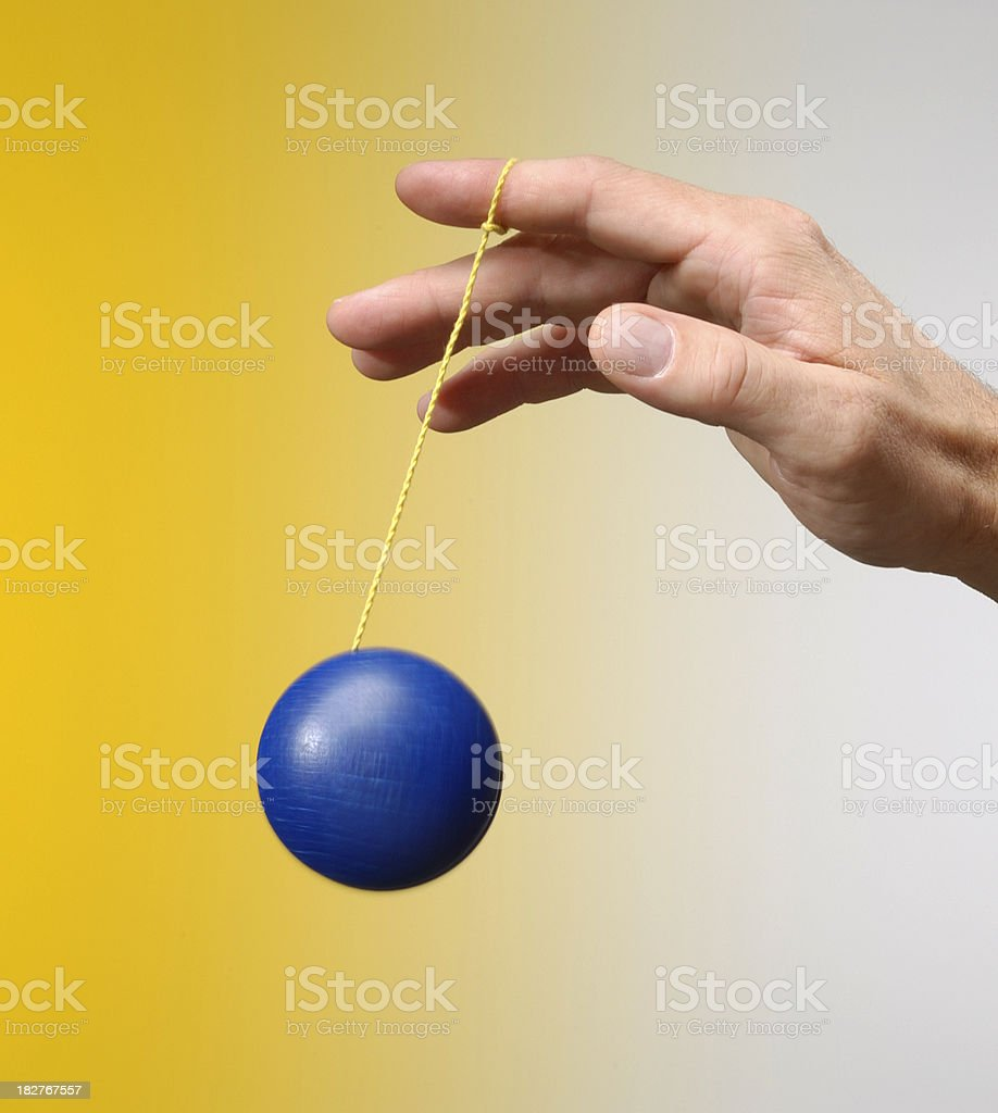 Male hand playing with a blu yo-yo on yellow background royalty-free stock photo