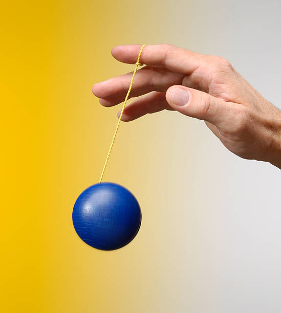 Male hand playing with a blu yo-yo on yellow background stock photo