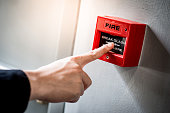 Male hand pointing at red fire alarm switch