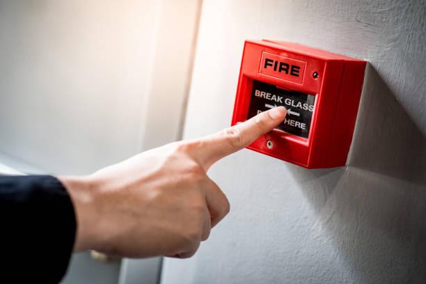 Männliche Hand zeigt auf roten Feueralarmschalter – Foto