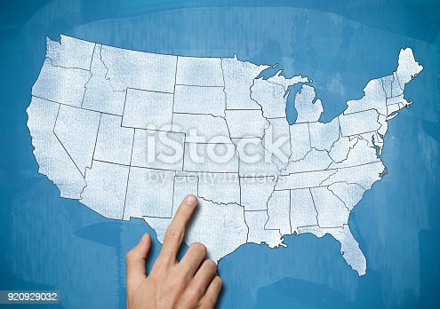 520945644 istock photo Male hand pointing on USA map / Blue board concept (Click for more) 920929032