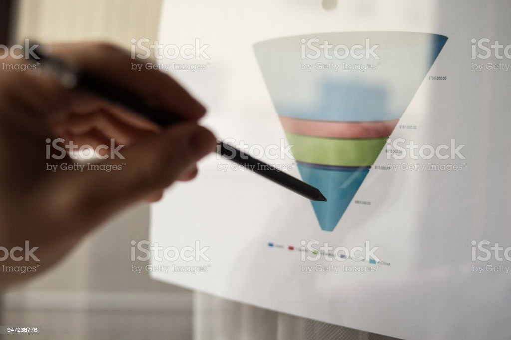 Male hand pointing with a pencil at a sales funnel chart during a business meeting in office stock photo