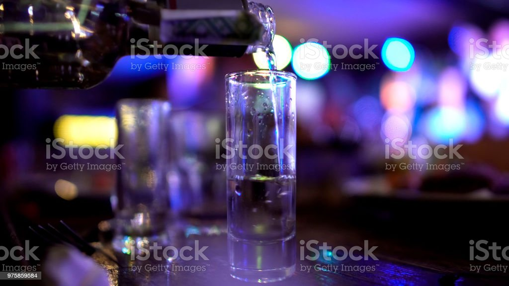 Male hand pouring in huge shot of vodka, alcoholism issues, failed abstinence stock photo