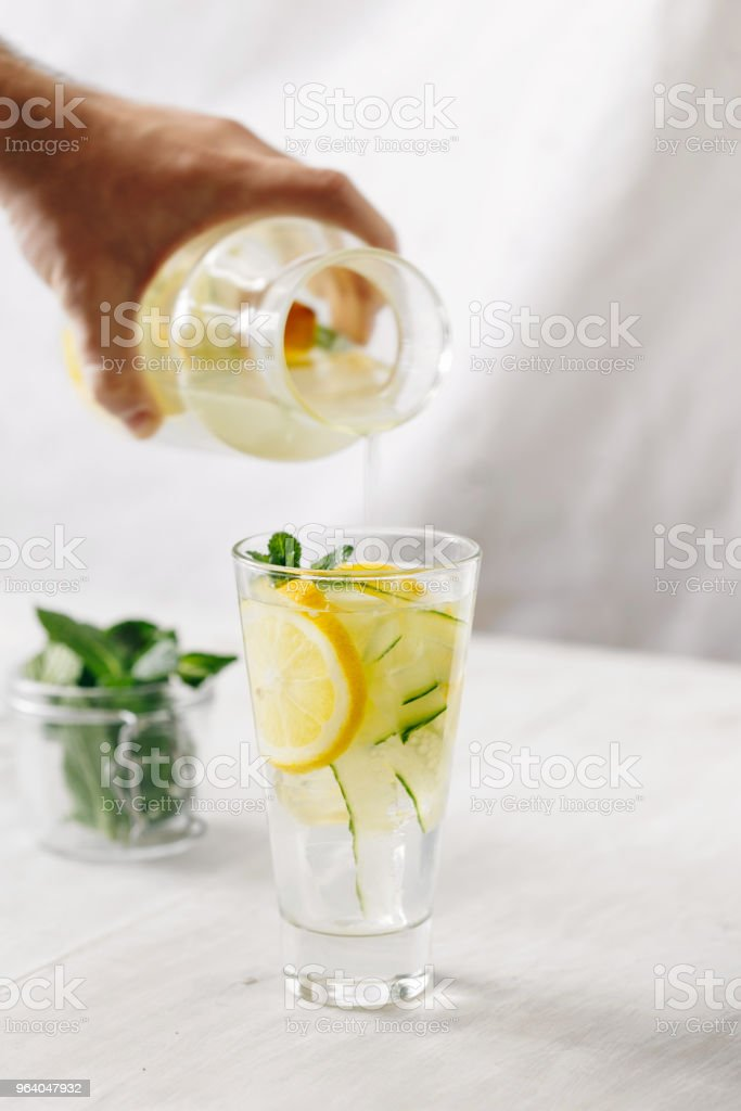 Male hand pours detox water into glass. Detox water, fitness, healthy nutrition diet concept. Fresh lemon cucumber mint detox drink in glass on white wooden table - Royalty-free Adult Stock Photo