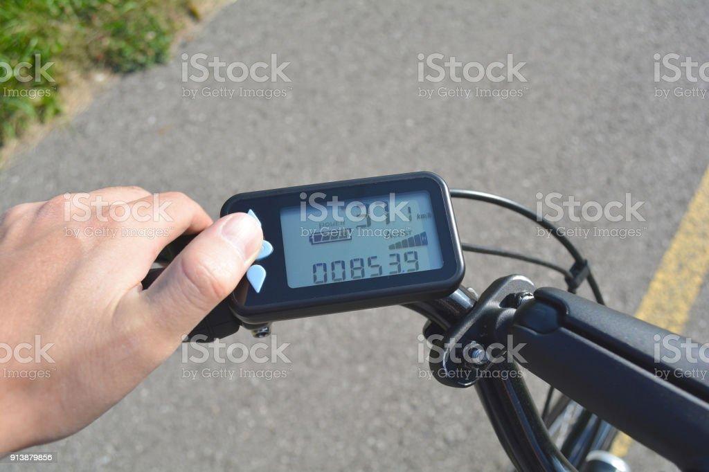 Una mano masculina presiona un botón en un scooter negro bicicleta electrónica. Ordenador para bicicleta instalado en el manillar de la bicicleta. Hombre presionando un botón en el tablero de control de la bicicleta. - foto de stock
