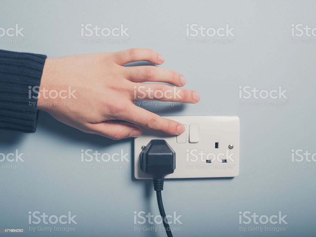 Male hand pressing a power switch on the wall royalty-free stock photo
