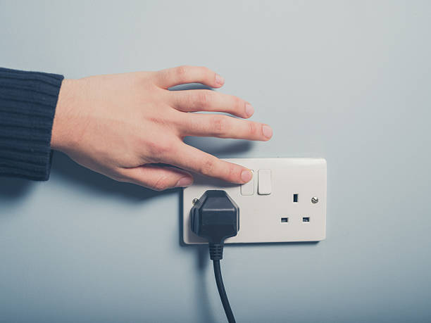 Male hand pressing a power switch on the wall stock photo