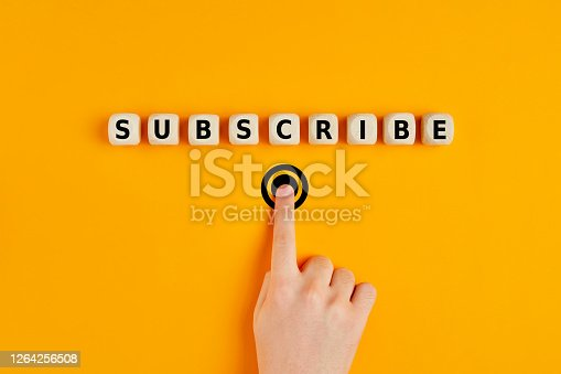 Male hand pressing subscription button with the word subscribe written on wooden blocks. Online registration concept.