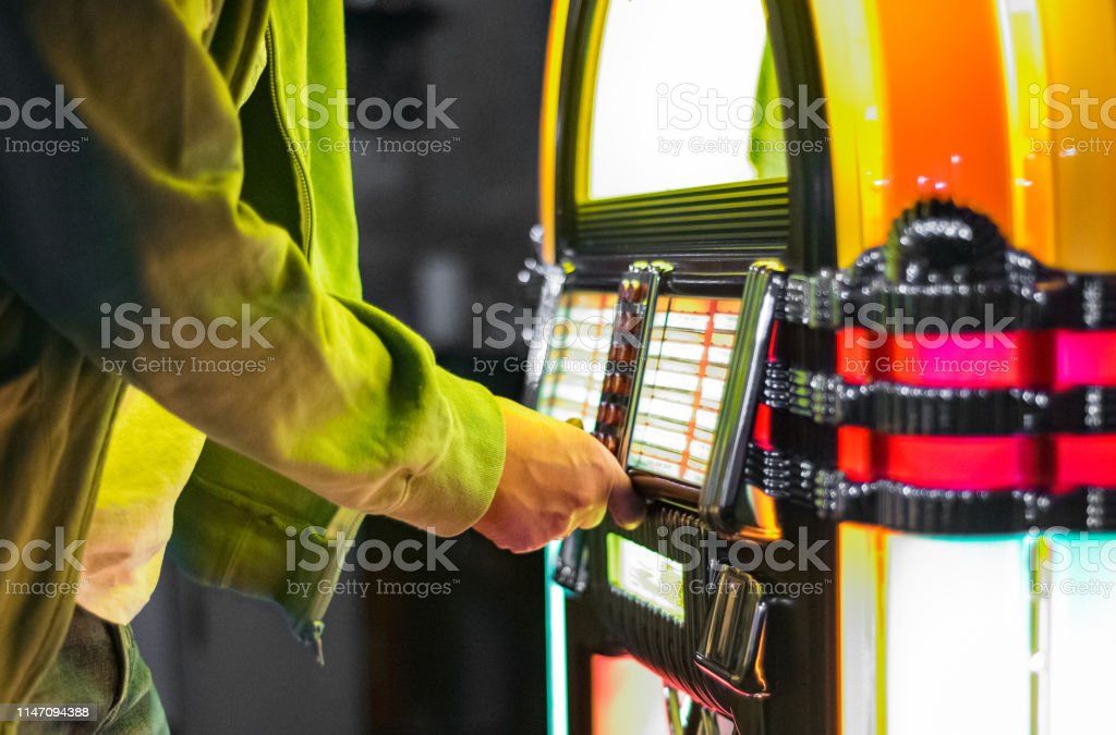 Male Hand Pushing Buttons To Play Song On Old Jukebox