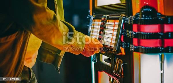 istock Male hand pushing buttons to play song on old Jukebox, selecting records 1211159040