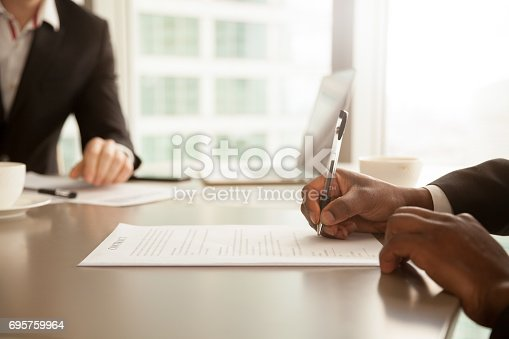 istock Male hand putting signature, signing partnership contract concept, close up 695759964