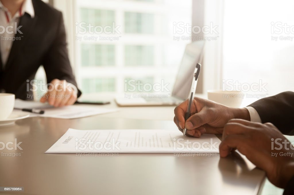 Male hand putting signature, signing partnership contract concept, close up stock photo