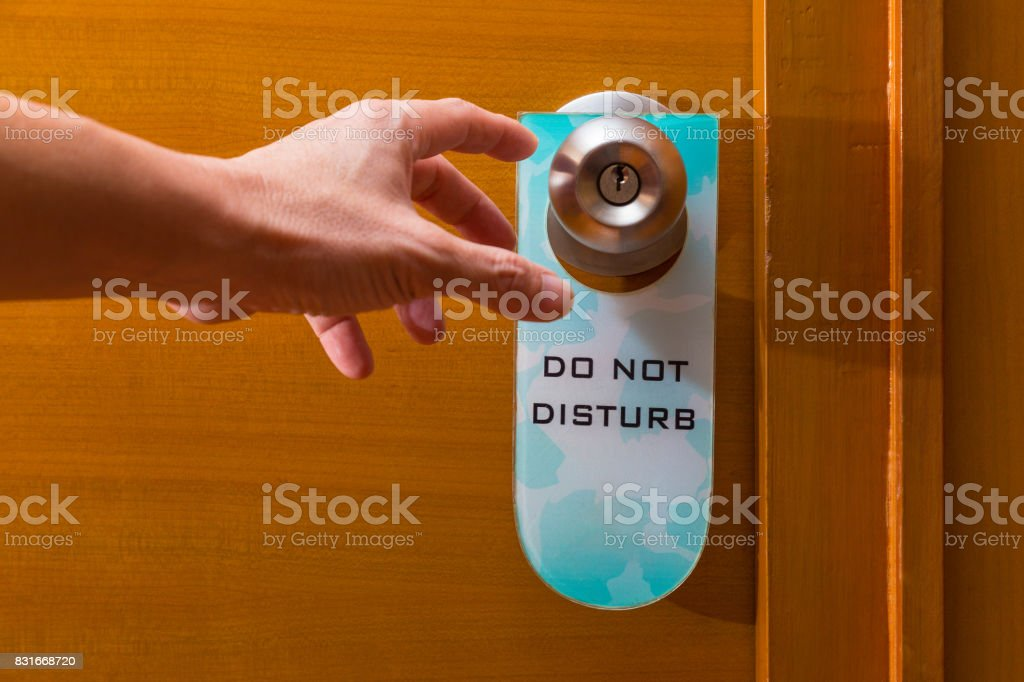 male hand reaching to metal door knob with old Do Not Disturb sign tag haning on, concept of needing privacy or privacy about being intruded stock photo