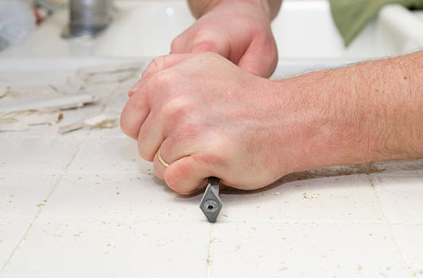 Male hand removing grout from kitchen tiles stock photo