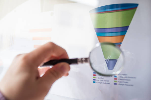 male hand showing a sales funnel chart with a magnifier lens during a business meeting in office - sales funnel stock photos and pictures