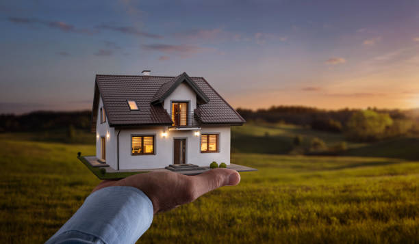 Male hand showing, offering a new dream house at the empty field with copy space Concept of buying or building a new home. Male hand showing, offering a new dream house at the empty field with copy space model home stock pictures, royalty-free photos & images