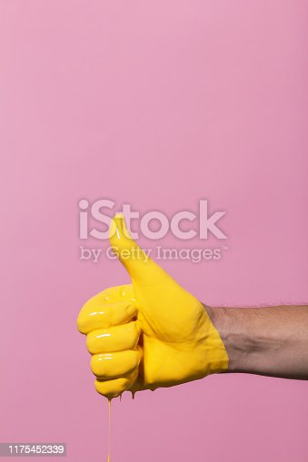 istock male hand showing sign thumb up with paint flowing down on a colored background. creative idea, creative concept, gesture