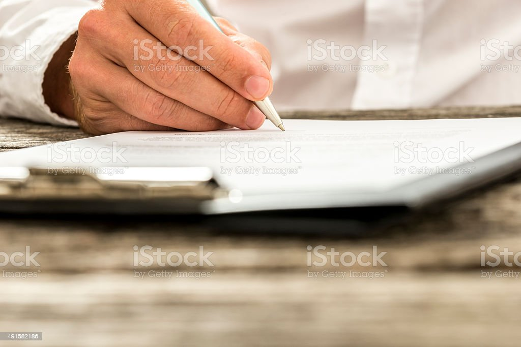 Male hand signing subscription form, legal document or business contract stock photo