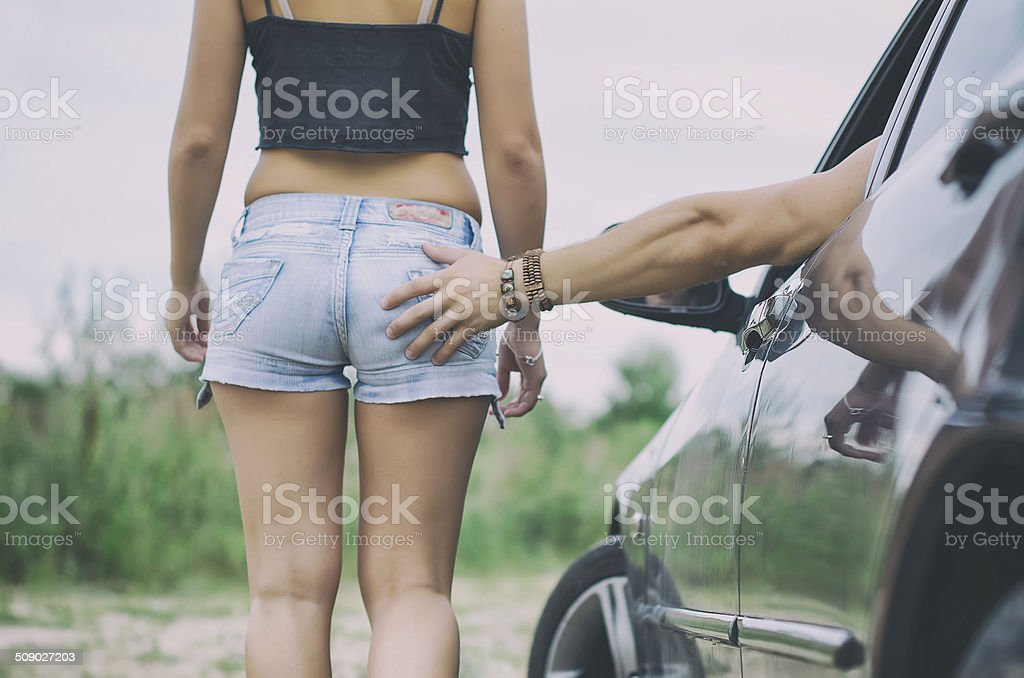 Male hand slaps the girl's ass. stock photo