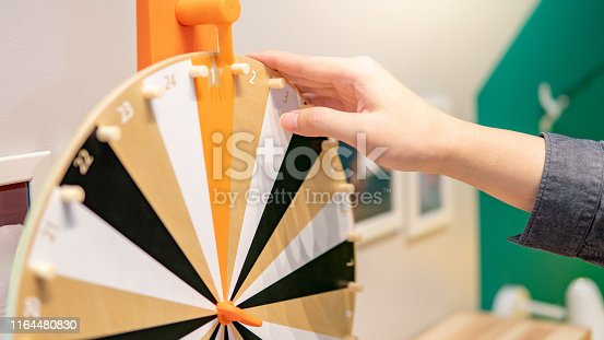 Male hand spinning wooden wheel of fortune. Luck and risk game. Entertainment gaming concept