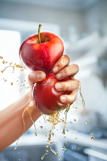 A male hand squeezes fresh juice. Pure apple juice pouring out from fruit into glass stock photo