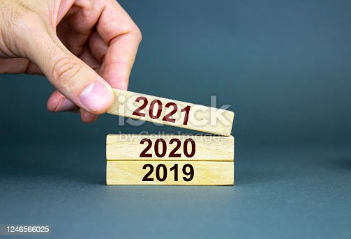 873333520 istock photo A male hand stacks wooden blocks with numbers 2019, 2020, 2021. 1246566025