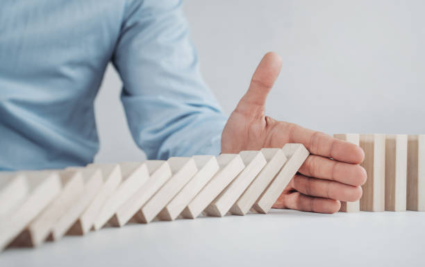 Male hand stopping the domino effect stock photo