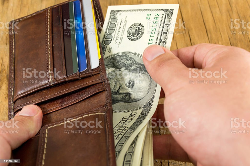 Male hand taking dollar out of wallet stock photo