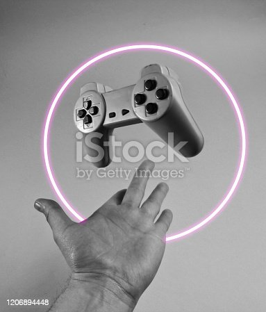 istock Male hand throwing up a gamepad. 80's synth wave and retrowave glowing circle futuristic aesthetics. Old fashioned abstraction concept 1206894448