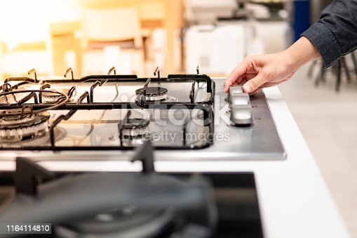 Male hand turning switch knob on modern gas stove in kitchen showroom. Cooking appliance in domestic kitchen. Home improvement and House interior design concepts