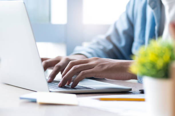 Male hand typing on laptop keyboard. stock photo