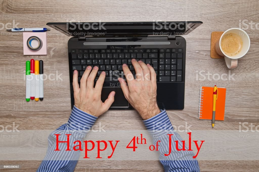 Male hand typing on laptop, message Happy 4th of July stock photo