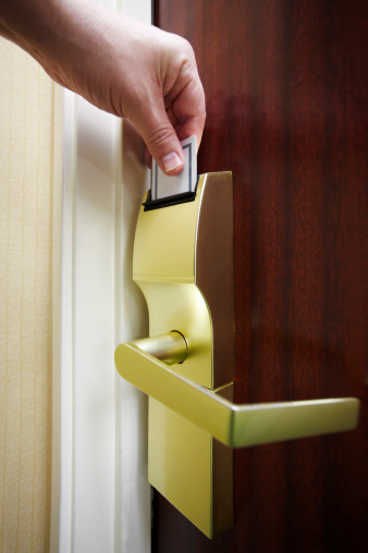 Vertical stock photo of a male hand unlocking a hotel room door electronic lock with a keycard.