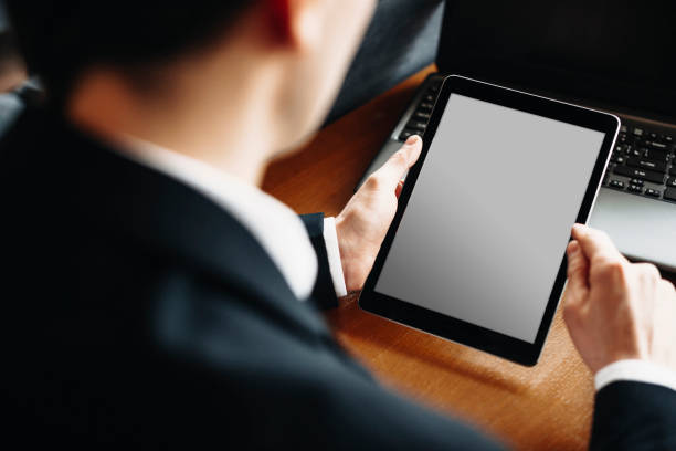 Male hand using a tablet while sitting at a desk with a laptop on the desk. stock photo