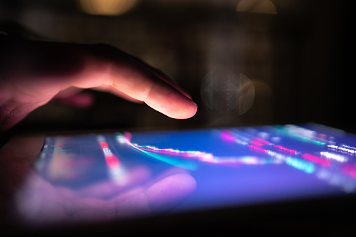 Male hand using digital tablet / smartphone at night