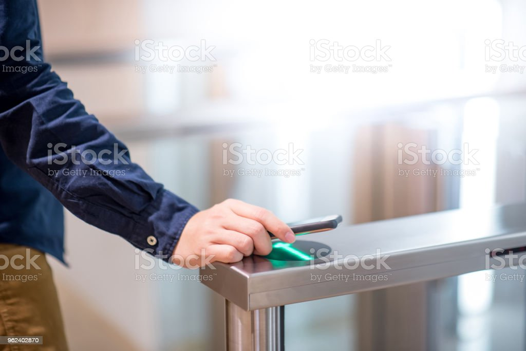 Male hand using smart card to open automatic gate machine in office building stock photo