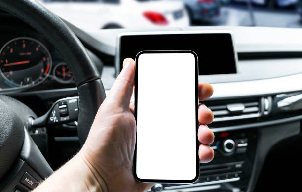 Male hand using smartphone in car. Man driving a car. Smartphone in a car use for Navigate or GPS. Mobile phone with isolated white screen. Blank empty screen. copy space. Empty space for text. stock photo