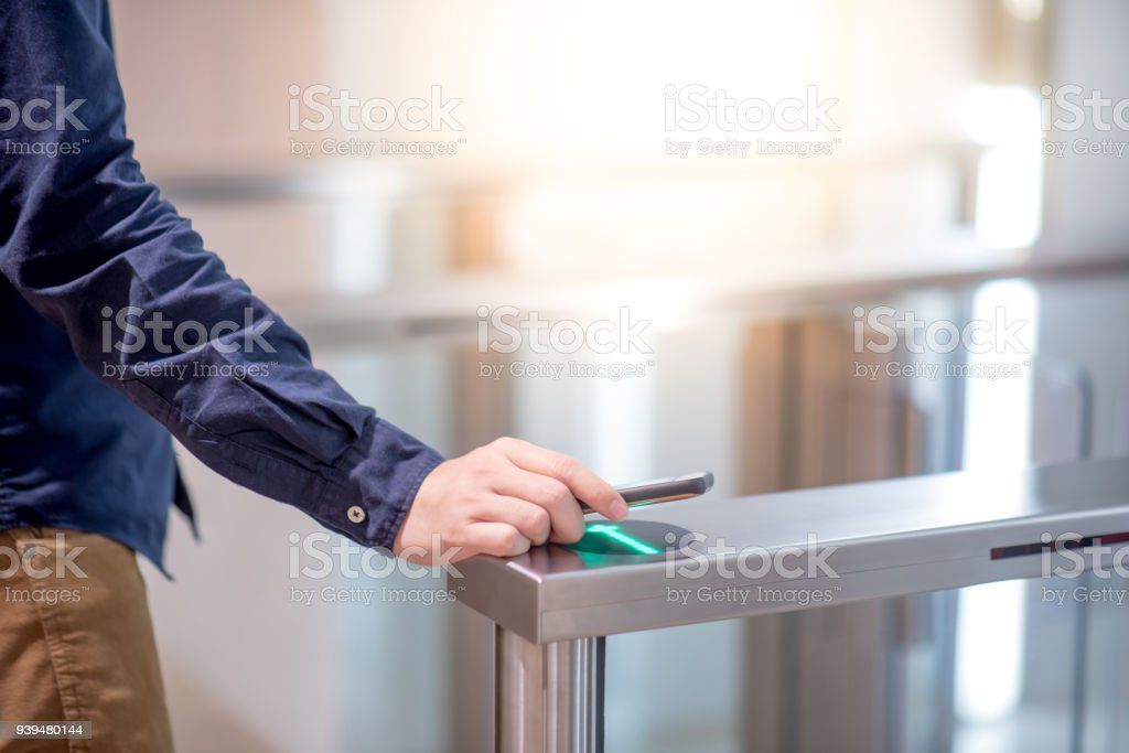 Male hand using smartphone to open automatic gate machine in office building stock photo