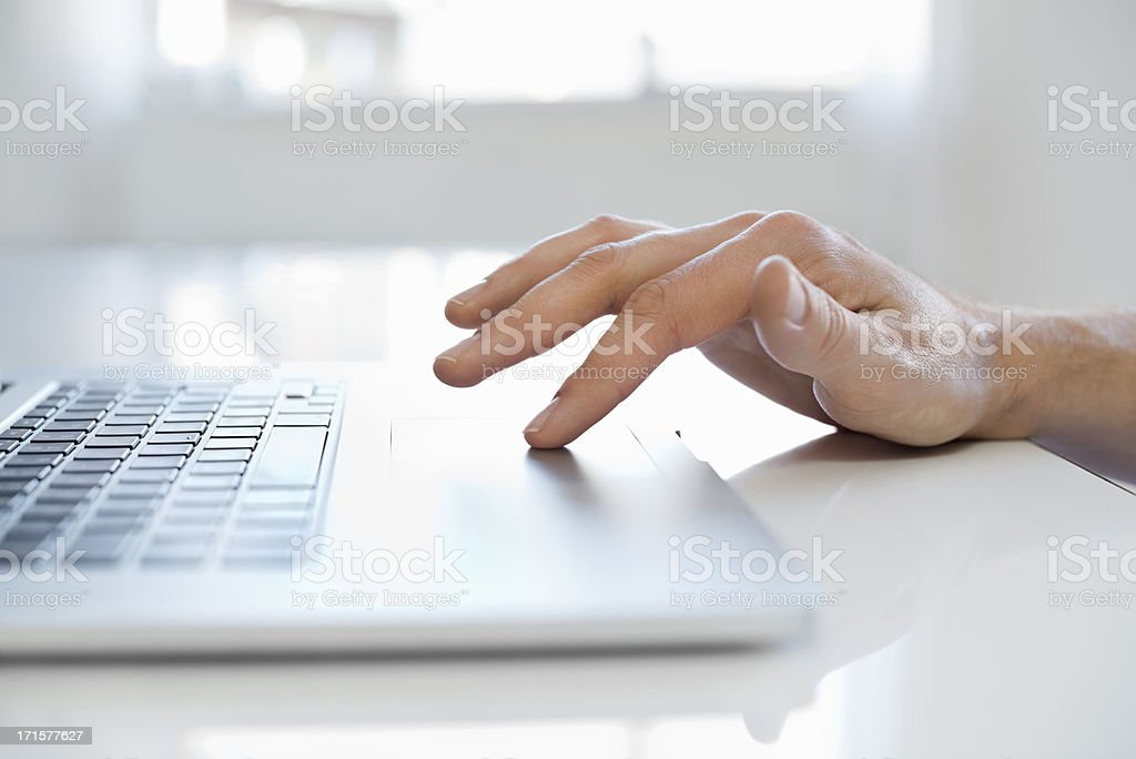 Male Hand Using Touchpad On Laptop stock photo