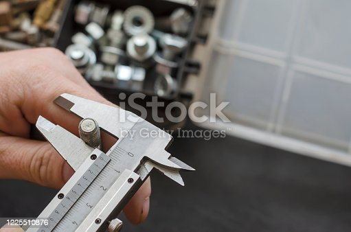 A male hand with a caliper measures the diameter of a bolt. Choosing the right metal fastener. Use of manual measuring instruments. Focus in the foreground. Close-up.