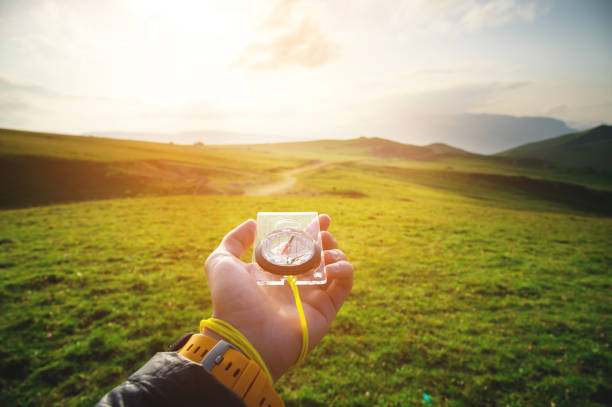 Male hand with a magnetic compass ea against the backdrop of a beautiful landscape at sunset. stock photo