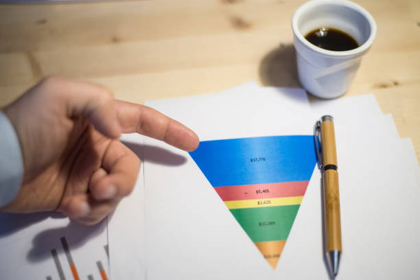 male hand with a pen pointing at a sales funnel chart during a business meeting - sales funnel stock photos and pictures