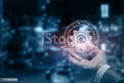 istock A male hand with an update cogwheel inside a digital sphere. 1137632555