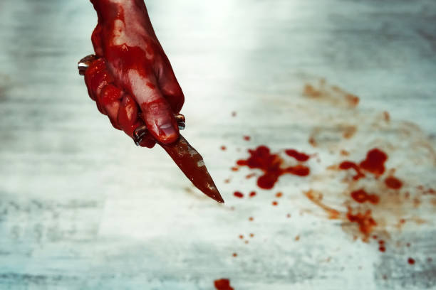 Male hand with bloody knife over concrete wall stock photo